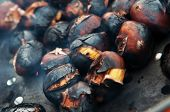 Close-up Of Scorched Chestnuts Roasting On An Open Fire In A Pan With Holes poster