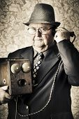 foto of olden days  - Image of a old fashioned vintage business man standing in a office communicating to the exchange through a retro box telephone in a technology concept - JPG