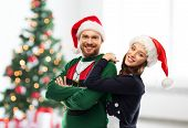 people and holidays concept - portrait of happy couple in santa hats at ugly sweater party over chri poster