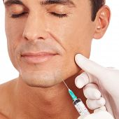 Attractive man at plastic surgery with syringe in his face