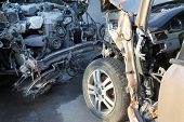 Broken hoods with bare motors of two collided cars after accident