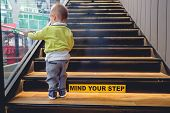 Asian Toddler Boy Climbs Up The Wooden Stairs poster