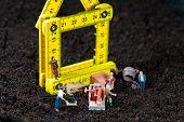 Miniature Workmen Building A House