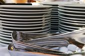 Three Stacks Of White Catering Plates With Siver Tongs
