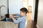 Little Boy Washing Dishes And Cleaning The Kitchen After Making Dinner poster