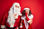 Middle age couple wearing Santa costume and glasses over isolated red background hand on mouth telli poster