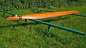 Parked Wooden Canoe Inverted Upside Down To Dry On A Metal Tubular Support On The Green Foliage Back poster