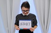 Mature Woman Holding Notepad With Hand Written Start Word. Start Of Business, New Year, Relationship poster