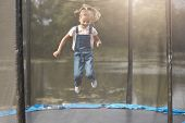 Outdoor Shot Of Girl Jumping On Trampoline, Blonde Female Child With Ponytail Wearing White Shirt An poster
