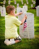 Child straightening flags at veterans cemetery during Memorial Day weekend