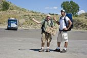 picture of semi-arid  - Hitch Hikers at a truck stop with a sign - JPG