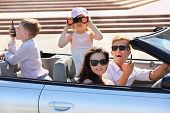 Happy father, mother and two children ride in convertible car and play spies at sunny day; focus on woman