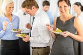 picture of buffet lunch  - Smiling business woman during company lunch buffet hold salad plate - JPG