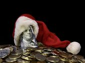 One Hundred Dollars In A Christmas Hat. Dollars On Top On Foreign Metal Coins. Banknote With Benjami poster