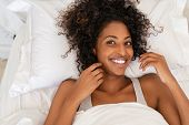 Beautiful young woman lying on bed in the morning and laughing. Top view of african american girl ly poster