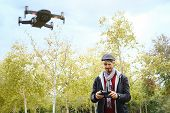 Young Man With Remote Control Learning To Fly Quadcopter Drone poster