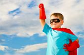 stock photo of guardian  - Child pretending to be a superhero outdoors under cloudy blue sky - JPG