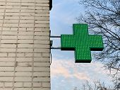 Urban Pharmacy Or Drug Store Sign, Led Display Green Cross On The Wall In The City Street, Copy Spac poster