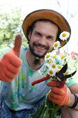 Man Holding The Camomile Bouquet And The Garden Prune And Showing  Thumb Up