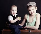 vintage art portrait of little boy with his baby brother leaning on old suitcase, retro stylization