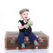portrait of little baby boy sitting on old vintage suitcase, retro stylization of 30-50s