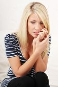 Stressed young woman eating her nails