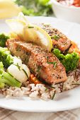 Grilled salmon steak with cooked rice, herbs and vegetables