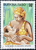 stamp printed in Burkina Faso shows a mother breastfeeding her child