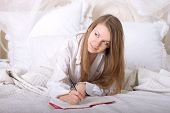 Girl writes a diary while lying in bed in the morning