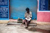 THANJAVUR, INDIA - FEBRUARY 14: Beggar sitting on a street February 14, 2013 in Thanjavur, India. Po