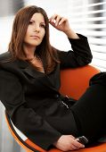 pensive businesswoman with cell phone in office
