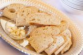 Tray of Fresh Made Sourdough Bread with Garlic Cloves on a Serving Table.