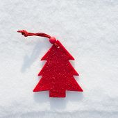plushy red fir tree toy on snow background