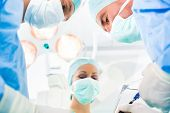 Hospital - surgery team in operating room or Op of a clinic operating on a patient in an emergency situation