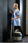 Hotel room service - young chambermaid standing in front of a suite door in a hotel with a vacuum cl
