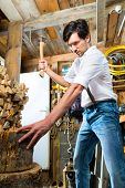 stock photo of wooden shack  - Young man chops firewood or wood with a hatchet or an axe in a shack in the mountains - JPG