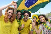 Group of happy Brazilian soccer fans commemorating victory, with the flag of Brazil swinging in the