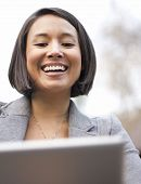 Attractive laughing woman having fun using her electronic wireless device