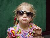 Funny girl in big glasses looks in the frame
