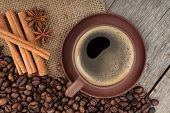 Coffee cup with spices on wooden table texture. View from above