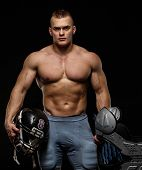 Man with naked muscular torso holding american football player accessories