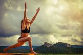 stock photo of surya  - Young woman makes sun salutation yoga pose - JPG