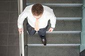 Sleek corporate man ascending stairs