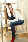 Lonely sad woman sitting on home ladder