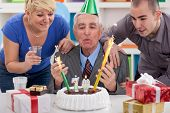 senior man blowing candles on birthday cake with family