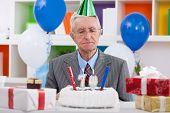 Senior man looking at his birthday cake for 70th birthday