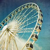 Retro style image of a ferris wheel against blue sky. Cross-processed, grunge effect.