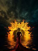 stock photo of fantasy world  - Woman in red dress at the gate of hell - JPG