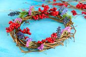 Wreath of dry branches with flowers and viburnum on wooden table close-up