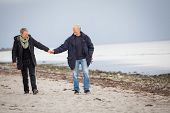 Mature Happy Couple Walking On Beach In Autumn